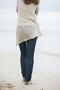 Closeup on woman in sweater walking on lonely beach young rear view Royalty Free Stock Photography