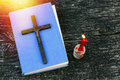 Closeup of wooden Christian cross on bible, burning candle and prayer beads on the old table. Royalty Free Stock Photo