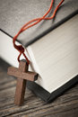 Closeup of wooden christian cross necklace next to holy bible Royalty Free Stock Image