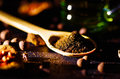 Closeup wooden rustic spoon filled up with fresh herbal tea powder, other teas and spices in background, very nice Royalty Free Stock Photo