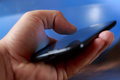 Closeup of young boys hand using smartphone. Blue blurred background Royalty Free Stock Photo