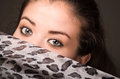 Closeup young brunette model posing with grey brown scarf covering half her face revealing beautiful eyes only, dark Royalty Free Stock Photo