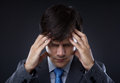 Closeup of young business man with headache Stock Photos