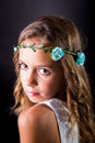 Closeup of a young girl with flower tiara and sober look long hair posing on black background Royalty Free Stock Image