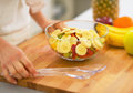 Closeup on young housewife making fruit salad Royalty Free Stock Photo