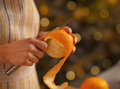 Closeup on young housewife removing orange peel in kitchen Stock Images