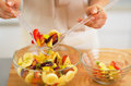 Closeup on young housewife serving fruit salad Royalty Free Stock Photo
