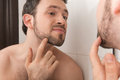 Closeup of young man examining his stubble in mirror looks at beard and thought about shaving Stock Photo