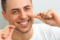 Closeup of young man flossing his teeth. Cleaning teeth with den Royalty Free Stock Photo