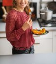 Closeup on young woman eating baked pumpkin in kitchen Royalty Free Stock Photo