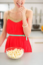 Closeup on young woman eating popcorn in kitchen Royalty Free Stock Photo