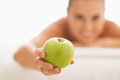 Closeup on young woman on massage table giving apple in spa salon Royalty Free Stock Images
