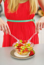 Closeup on young woman mixing fresh fruits salad in modern kitchen Royalty Free Stock Images