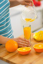 Closeup on young woman pouring fresh orange juice Royalty Free Stock Photo