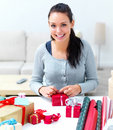 Closeup of a young woman sitting and wrapping gift Royalty Free Stock Photo