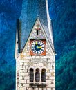Closup view of protestant church`s clock on high tower in Hallstatt, Austria Royalty Free Stock Photo