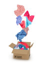 Clothes falling into the cardboard box on white Stock Image
