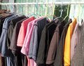 Clothes hanging colored clothing variety of casual t shirts on wooden hangers Royalty Free Stock Images