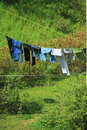 Clothes hanging to dry on a laundry line against green hill Royalty Free Stock Photo