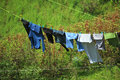Clothes hanging to dry on a laundry line against green hill Stock Photo