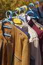 Clothes and leather jacket displayed at garage sale second hand jackets for flea market Stock Photos