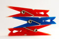 Clothes pins laying on each other red and one blue one Royalty Free Stock Image