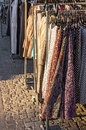 Clothes street sale clothing on a rack in evening sunlight Royalty Free Stock Image