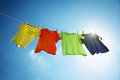 Clothesline and laundry t shirts hanging on a in front of blue sky sun Stock Image