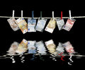 Clothesline and money with some euro banknotes fixed with clothes pins on reflective water surface in black back Royalty Free Stock Photography