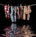 Clothesline and sox with some multicolored fixed with clothes pins over reflective water surface in black back Royalty Free Stock Photo