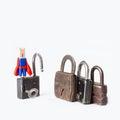 Clothespin superhero housebreaker with opened padlock vintage retro design closed iron padlocks opening conceptual photography Royalty Free Stock Image