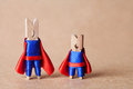 Clothespins superheroes in blue suit and red cape. Teamwork conceptual image Royalty Free Stock Photo