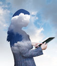 Cloud computing businesswoman using a computer tablet composited with clouds Royalty Free Stock Photos