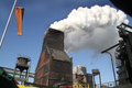 Cloud of steam from coke oven quenching station with wind indicator and blue sky Royalty Free Stock Photo