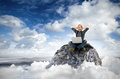 Cloud surfing a man with laptop sits on a rock in the clouds Stock Photos