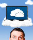 Cloud technologies man is looking at modern laptop in skies Royalty Free Stock Photo