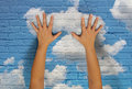Cloud technology concept a pair of hands reaching up and touching a brick wall with clouds painted onto the surface for the Royalty Free Stock Images