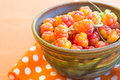 Cloudberries in ceramic bowl on orange background Royalty Free Stock Photos