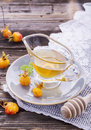 Cloudberry honey in a gravy boat on saucer with ripe berries arctic cloudberries
