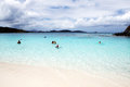Clouded day tourists are swimming at trunk bay at st john island in american virgin islands in a Stock Photography