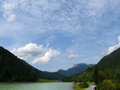 Clouded sky a above a lake and a mountain Stock Images
