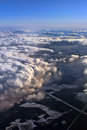 Clouds above the ground the snow covered fields view from airplane Stock Photography