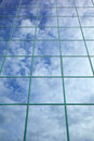 Clouds blue sky reflected glass facade office building Royalty Free Stock Photos