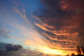 Clouds of different shapes and colors before sunset. Dramatic sky colors at sunset - blue, orange, golden. Royalty Free Stock Photo