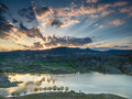Clouds illuminated rising sun and reflected in the lake Royalty Free Stock Images