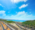 Clouds over capo testa coastline wooden boardwalk under a cloudy sky in sardinia Stock Photography