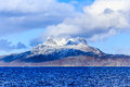 Clouds over Sermitsiaq mountain covered in snow with blue sea in Royalty Free Stock Photo