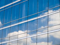 Clouds reflected in windows of modern office building Stock Images