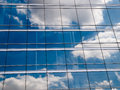 Clouds reflected in windows of modern office building Royalty Free Stock Image