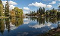 Clouds reflecting mirror pond bend in downtown is almost perfectly still in this autumnal image of peace located on the deschutes Royalty Free Stock Photography